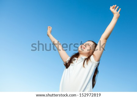 A portrait of a cute little girl, she is standing outside, wearing a white shirt against a blue sky, she has her arms up in the air, she looks very happy. - stock photo