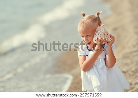 A portrait of a cute little smiling girl in white clothes playing with a shell on the beach on a warm sunny summer day. Holidays at sea. Funny kids - stock photo