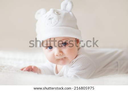 A portrait of a cute newborn baby girl in a white like a bear cub hat lying on its stomach