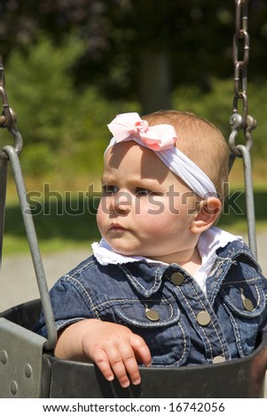A portrait of a cute one year old girl on a swing. Shallow depth of field.