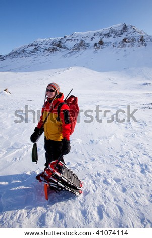 A portrait of a female adventurer against a mountain landscape - stock photo