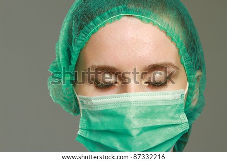 A portrait of a female doctor in a uniform - on grey background - stock photo