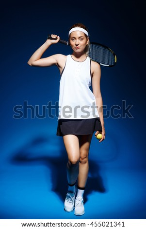 A portrait of a female tennis player with a racket on the shoulder - stock photo