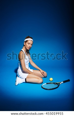 A portrait of a female tennis player with racket and ball aside sitting on floor in studio - stock photo