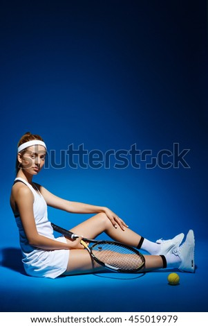 A portrait of a female tennis player with racket sitting on floor in studio - stock photo