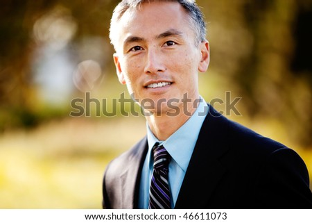 A portrait of a friendly Asian looking business man - stock photo