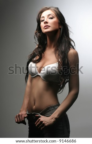 a portrait of a girl with a bra and jeans - stock photo