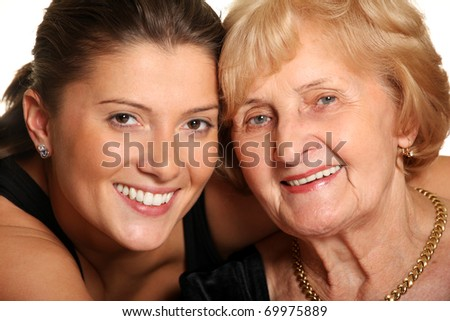 A portrait of a granddaughter hugging her grandma over white background - stock photo