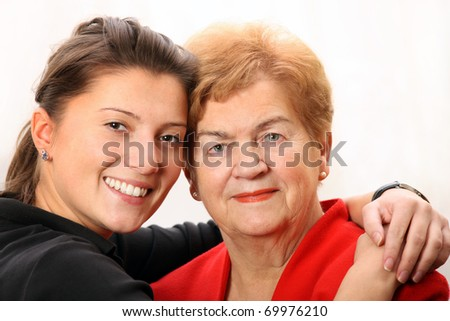A portrait of a granddaughter posing with her grandma over white background - stock photo