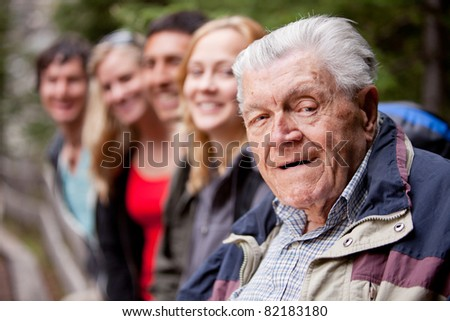A portrait of a grandfather type man with a group of young people - stock photo