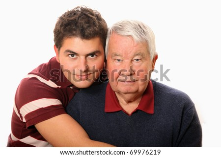 A portrait of a grandson standing with his grandpa against white background - stock photo
