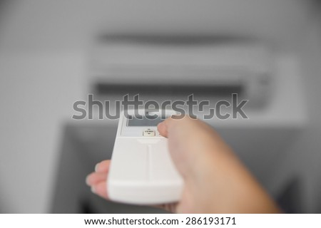 A portrait of a hand using a remote to activating air conditioning machine - stock photo