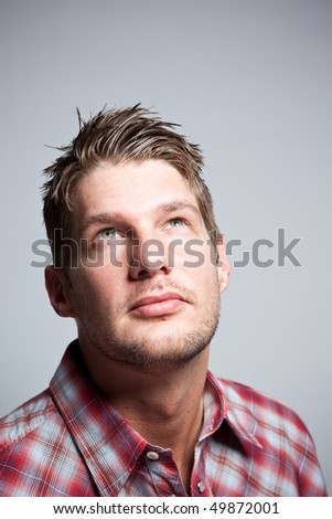 A portrait of a handsome caucasian man looking up - stock photo
