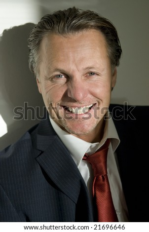 A portrait of a handsome forties businessman smiling towards the viewer - stock photo