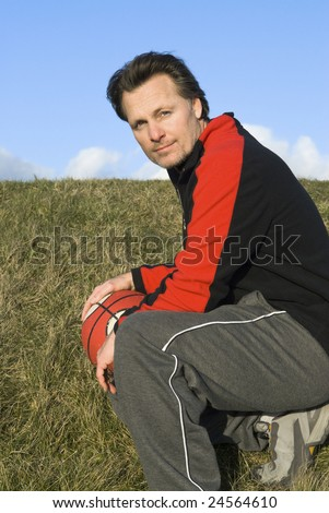 A portrait of a handsome forties sportsman with his basketball. - stock photo