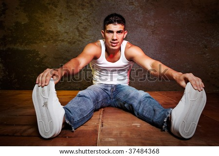 A portrait of a handsome hispanic male sitting on the floor