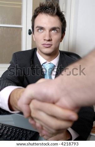 A portrait of a handsome young businessman shaking hands with person out of picture.