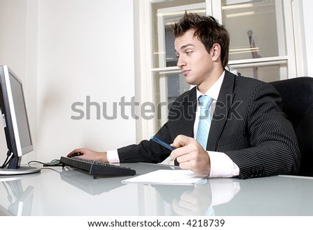 A portrait of a handsome young businessman sitting at the desk in office.