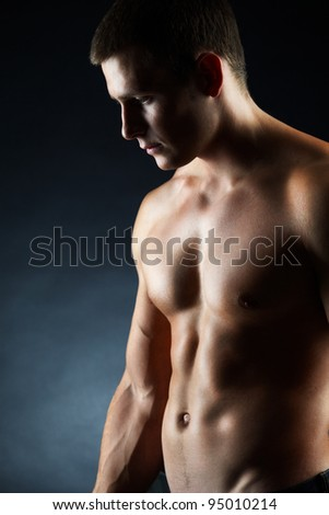 A portrait of a handsome young man without a shirt against dark background - stock photo