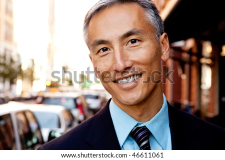 A portrait of a happy asian looking business man - stock photo
