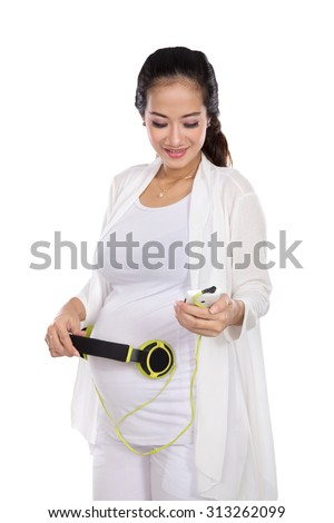 A portrait of a happy asian pregnant woman putting headphones on her belly. put some classical music on - stock photo