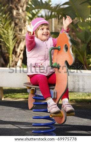 A portrait of a happy baby girl in the playground - stock photo