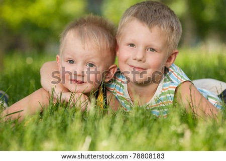 A portrait of a happy brothers on the grass in the park
