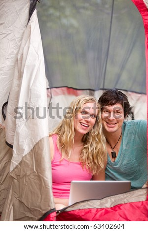 A portrait of a happy camping couple with a laptop, smiling at the camera - stock photo