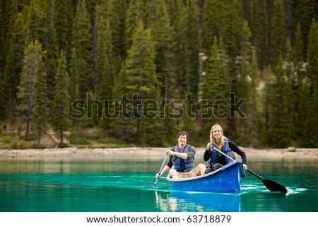 A portrait of a happy copule in a canoe on a glacial lake