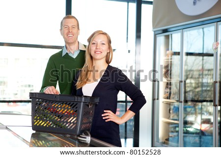 A portrait of a happy couple in a supermarket buying groceries - stock photo