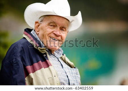 A portrait of a happy elderly man with cowboy hat - stock photo