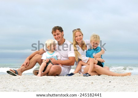 A portrait of a happy family of four, young, attractive caucasian people, including mother, father, baby, and child, are relaxing on a white sand beach by the ocean on a cloudy summer day. - stock photo