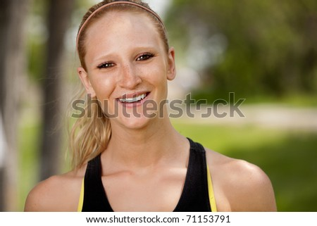 A portrait of a happy female jogger smiling at the camera - stock photo