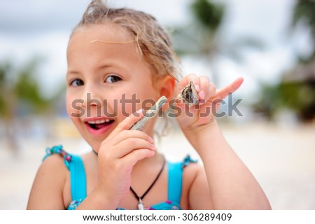 A portrait of a happy girl holding a hermit crab in her hand and pointing to it with a piece of coral - stock photo