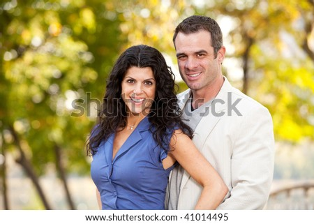 A portrait of a happy male and female in a park - stock photo
