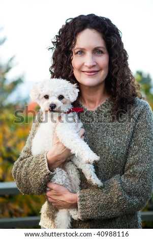 A portrait of a happy mature woman with her dog outdoor - stock photo