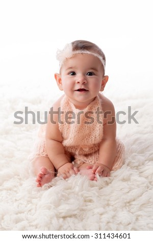 A portrait of a happy, 6 month old baby girl wearing a peach colored, knitted mohair romper. She is sitting on a cream colored sheepskin rug. - stock photo
