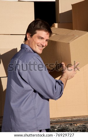 A portrait of a happy mover, moving cardboard boxes - stock photo