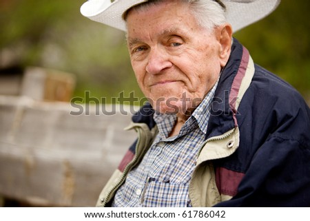 A portrait of a happy senior man on a bench - stock photo