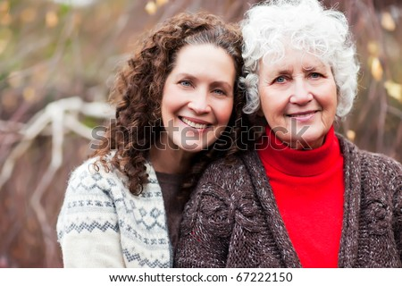 A portrait of a happy senior woman with her adult daughter - stock photo