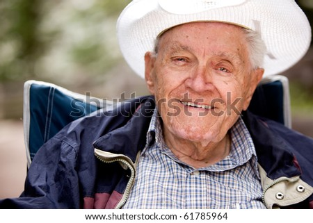 A portrait of a happy smiling elderly man sitting outdoors - stock photo
