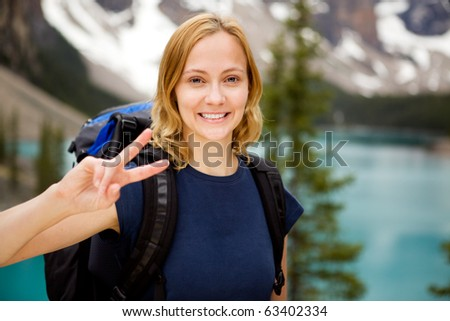 A portrait of a happy smiling girl with a mountain lake in the distant background - stock photo
