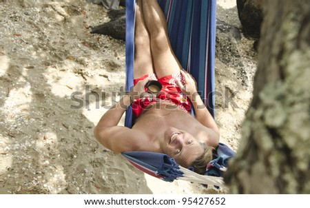 A portrait of a happy smiling man laying in a hammock on the beach. - stock photo