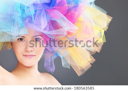 A portrait of a happy woman in a colorful hat posing over gray background - stock photo