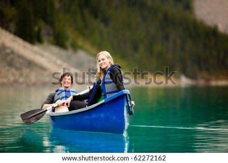 A portrait of a happy woman on a canoeing trip with a man - stock photo