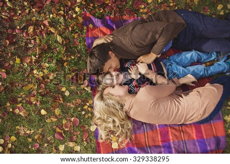 A portrait of a happy young family lay on a plaid and hug their son in a park in autumn. Top view - stock photo
