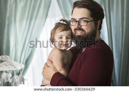 A Portrait of a happy young father with a baby at home - stock photo