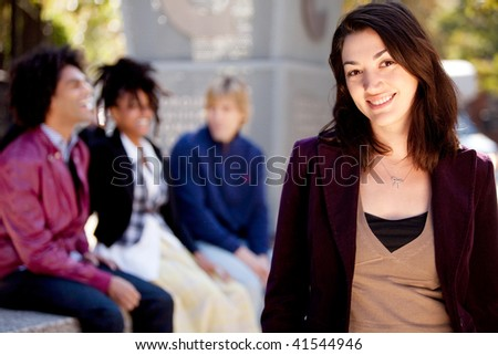A portrait of a happy young woman with friends - stock photo