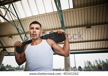 A portrait of a hispanic skateboarder outdoor - stock photo