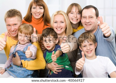 A portrait of a large prosperous family with their thumbs up - stock photo